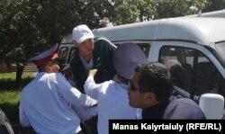 Полиция қызметкерлері ұсталған азаматты көлікке отырғызып жатыр. Алматы, 9 мамыр 2019.