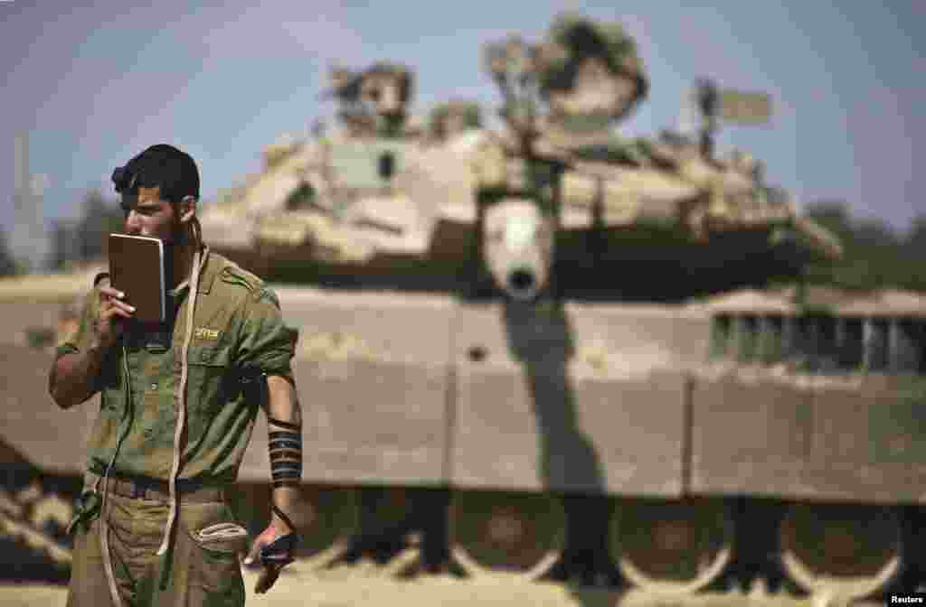 An Israeli soldier prays in front of a tank at a military staging area near the border with the Gaza Strip on July 24. (Reuters/Nir Elias)