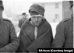 A captured Soviet soldier wears a borrowed hat.