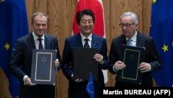 Прем'єр-міністр Японії Синдзо Абе (ц) виступає з головою Європейської Ради Дональдом Туском (л) та головою Європейської комісії Жан-Клодом Юнкером (п) після підписання угоди про вільну торгівлю, Токіо, 17 липня 2018 року