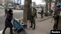 Жінка з дитиною проходить біля бойовиків угруповання «ДНР». Донецьк, березнь 2015 року