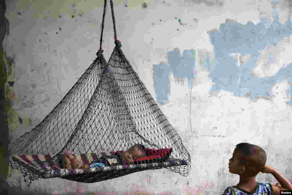 A son of a migrant fisherman from Burma rests in a hammock at a former shrimp warehouse where his family lives in Ban Nam Khem, Thailand. (Reuters/Damir Sagolj)