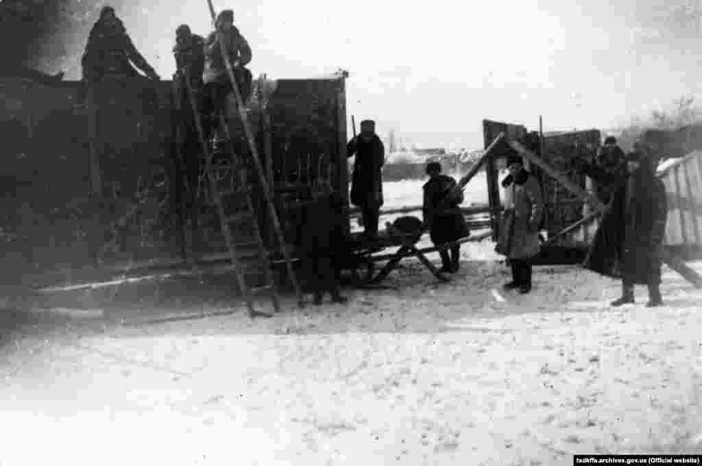 Чоловіки забирають майно у розкуркуленого селянина, Червоноармійський район Донецької області, 1930-і роки