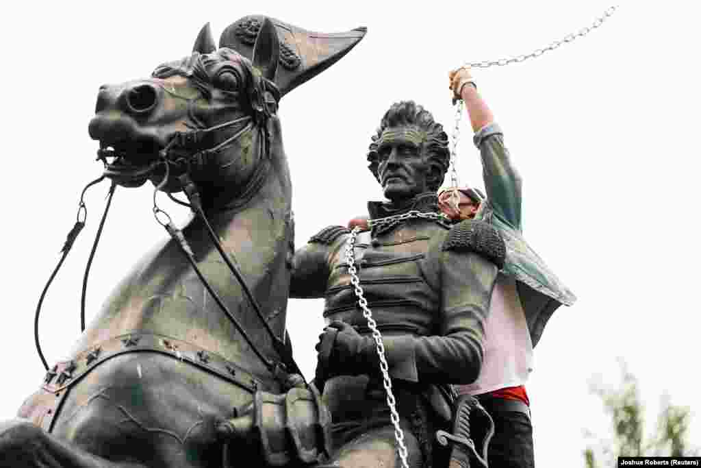 A protestor wraps chains around the neck of the statue of U.S. President Andrew Jackson during an attempt by protestors to pull the statue down in the middle of Lafayette Park in front of the White House during racial inequality protests in Washington, D.C., U.S., June 22, 2020.
