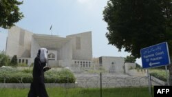 FILE: A pedestrian walks past The Supreme Court building in Islamabad.