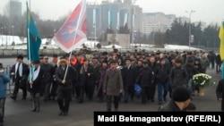 Гражданские активисты несут цветы к мемориалу, посвященному Декабрьским событиям. Алматы, 17 декабря 2010 года.