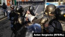 Полицијата приведува демонстрант на протестите во Москва