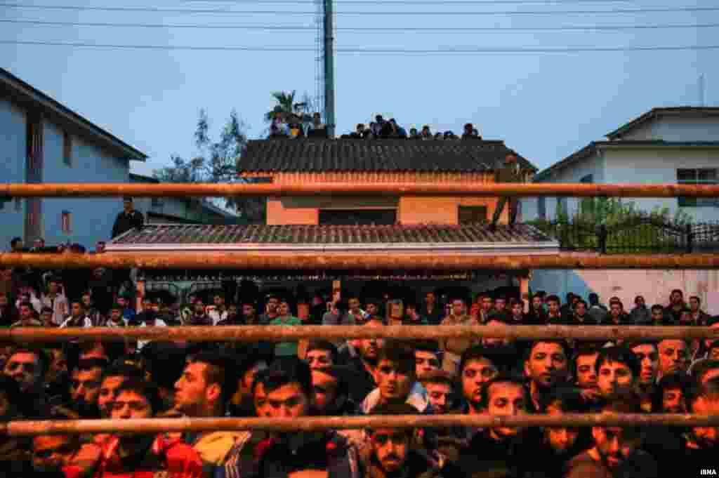 People gather to watch the planned execution in the town of Noor in Mazandaran Province.