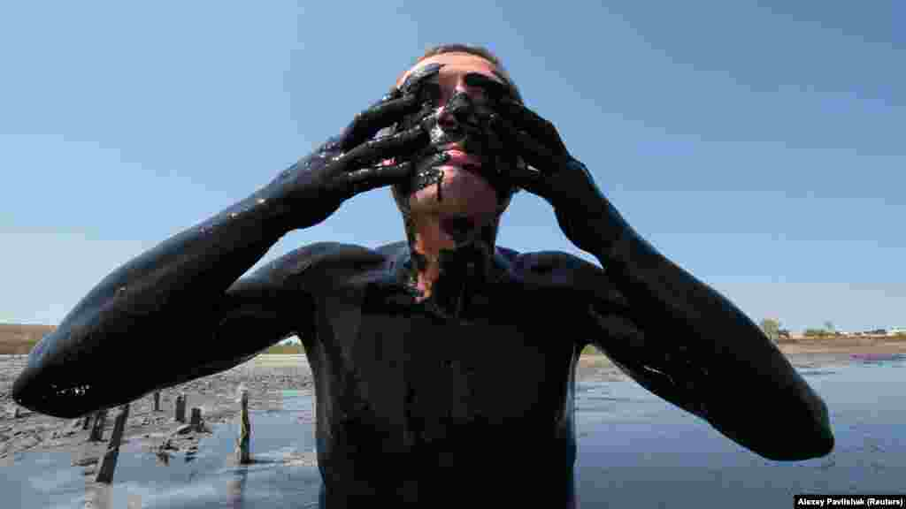 Відпочивальник намазує себе лікувальною гряззю з озера Чокрак, що блія села Курортне під Керчю