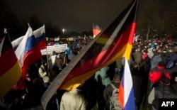 На демонстрациях правых популистов в Европе уже можно увидеть российские флаги. На снимке: митинг антиисламского движения ПЕГИДА в Дрездене, 5 января