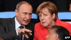 Brazil -- German Chancellor Angela Merkel (R) and Russian President Vladimir Putin chat during the second half of the 2014 FIFA World Cup final football match between Germany and Argentina at the Maracana Stadium in Rio de Janeiro, July 13, 2014