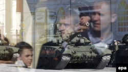 People are reflected in the glass of a bus stop as a Russian T-90 tank participates in the rehearsal for the Victory Day military parade on Red Square in Moscow.