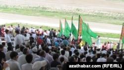 Türkmenistandaky aýlawlaryň birinde at çapyşyga tomaşa edýän adamlar