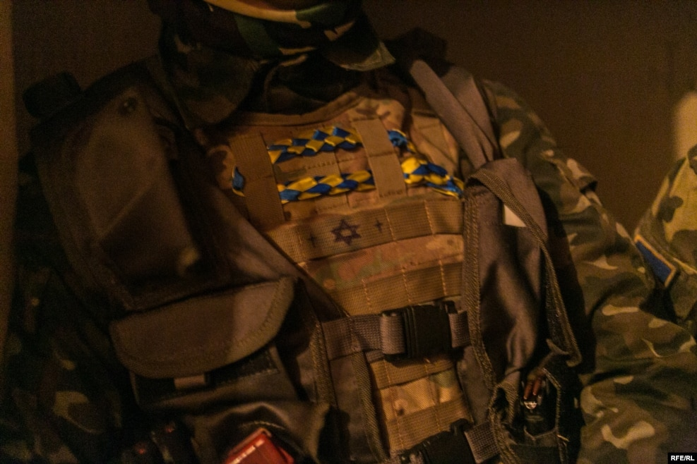 A soldier wears a bulletproof vest with a Star of David drawn on the front. Although the soldiers in this battalion are nationalists, they fight alongside a unit of Jewish volunteer soldiers, who also declare themselves to be Ukrainian nationalists.