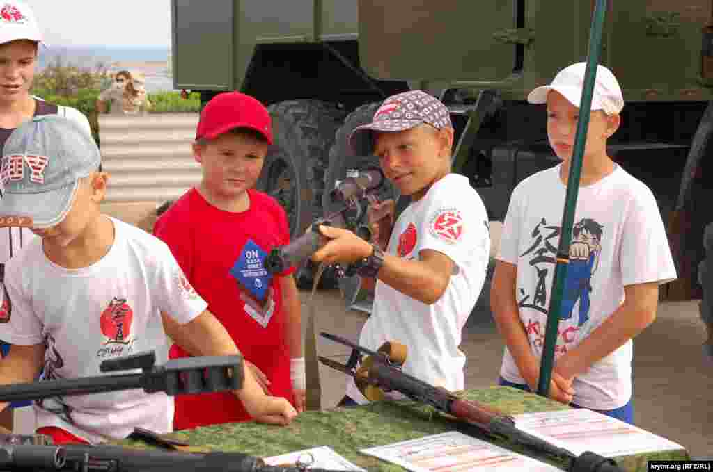 Мальчик прицеливается из снайперской винтовки
