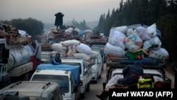 Тысячи сирийских беженцев направляются к турецкой границе. Снимок сделан 24 декабря 2019 в селении Хазано, примерно в 20 километрах северо-западнее города Идлиб.