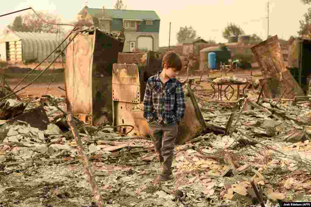 Jacob Saylors, 11, walks through the burned remains of his home in Paradise, California, on November 18.(AFP/Josh Edelson)