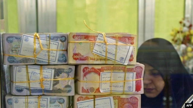 Iraqi dinars are stacked at a teller's window in a Najaf bank.