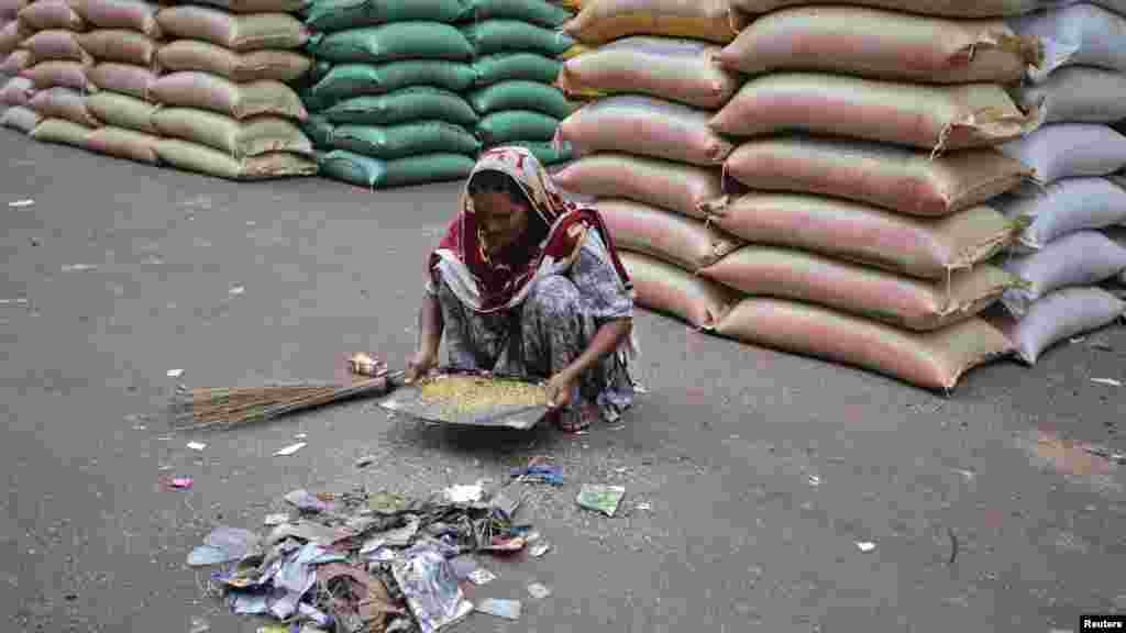 A Pakistani woman sorts out scraps of rice and lentils from a pile of waste near a supply warehouse at a wholesale market in Karachi on July 16. (REUTERS/Akhtar Soomro)