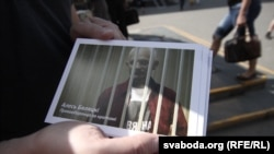 A supporter holds a flyer showing jailed rights activist Ales Byalyatski in Minsk.