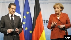 French President Nicolas Sarkozy (left) and German Chancellor Angela Merkel speak to reporters in Munich.