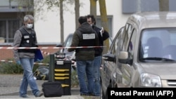 Police officers work near the site where Rahim Namazov and his wife were targeted by gunfire in Colomiers, France.