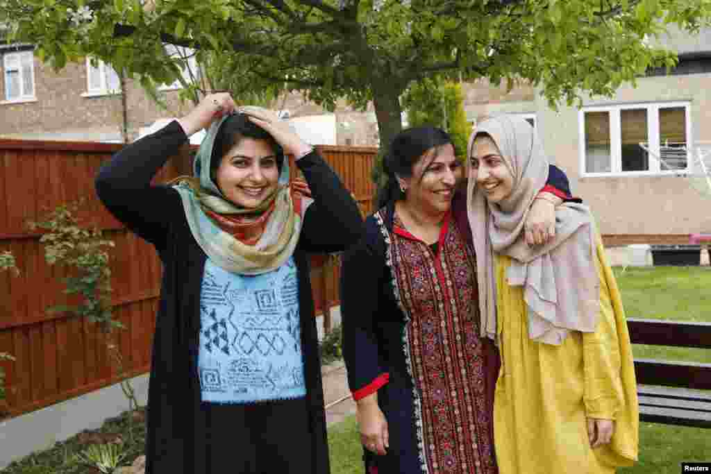 Sundas (left), her mother, Naheed (center), and her sister, Shanza, at their home in Walthamstow, east London. Sundas and Shanza started wearing the hijab in opposition to their parents' wishes. Their mother doesn't cover her head and didn't approve of her daughters' strict interpretation of Islam.