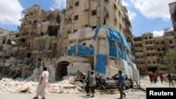 Люди оглядають пошкоджену авіаударом будівлю лікарні в Алеппо, 28 квітня 2016 року