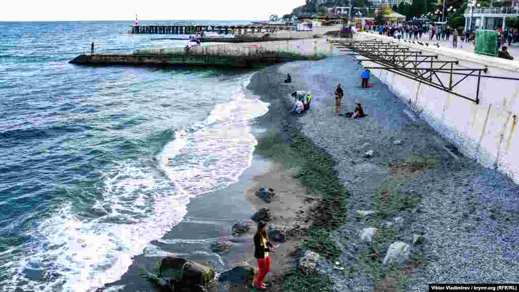 На пляже под набережной Алушты купающихся нет. Люди предпочитают сидеть возле берега
