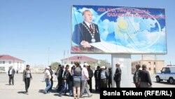 Работники предприятия «Мангистаугеология» проходят мимо билборда с изображением президента Казахстана Нурсултана Назарбаева. Поселок Курык Мангистауской области, 6 мая 2014 года.