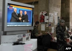 Пророссийские сепаратисты в Украине стоят рядом с телевизиром, по которому транслируется подписание Договора о создании Евразийского экономического союза.