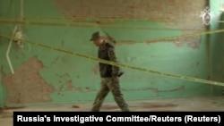 Следователь работает в поврежденном здании колледжа после нападения в Керчи. Скриншот видео, опубликованного российским Следкомом 19 октября 2018 года
