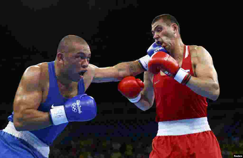 Juan Goncalves Nogueira of Brazil (left) lands a punch on Yevgeny Tishchenko during their men's 91-kilogram boxing event, won by Tishchenko.