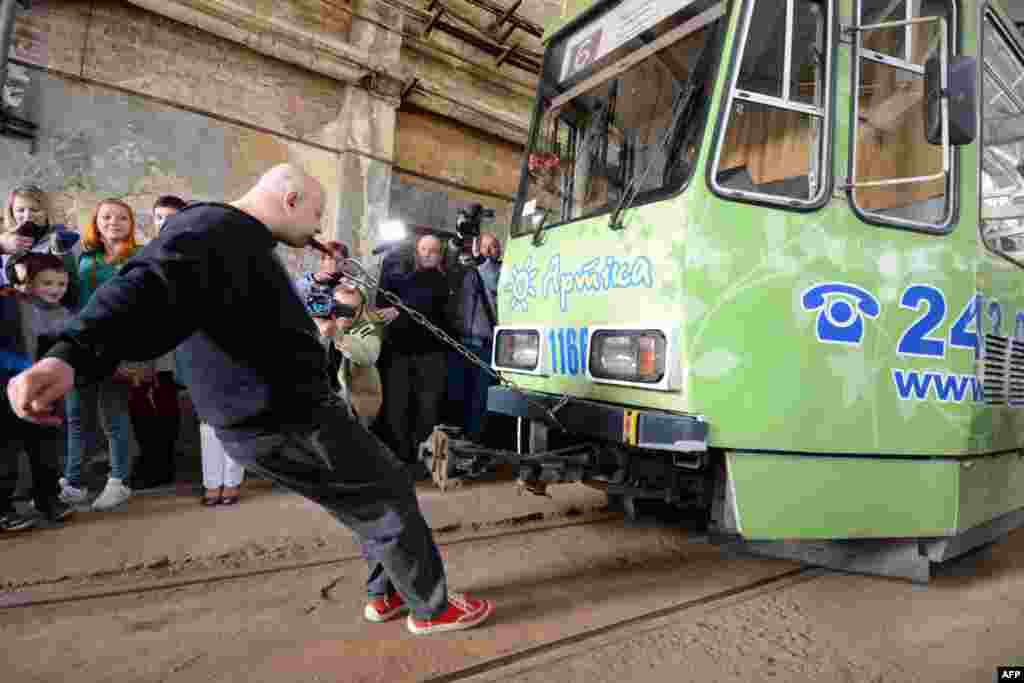 Ukrainian strongman Oleh Skavysh pulls a 19.5-ton tram a distance of 6.8 meters with his teeth to set a new world record in Lviv on November 4. (AFP/Yuriy Dyachyshyn)
