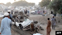 Pakistani residents gather at the site after a bomb blast in Bannu on November 26.