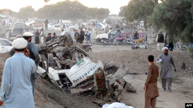 Pakistanis gather at the site of the bomb blast in Bannu on November 26.