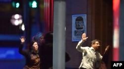Заложники выбегают из кафе в Сиднее, 16 декабря 2014 года.