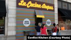"""Люди стоят в очереди за венесуэльской едой ресторана """"Конфликтная кухня""""."""