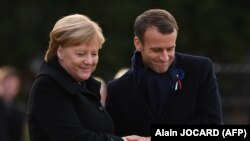 German Chancellor Angela Merkel (Left) and French President Emmanuel Macron take part in a ceremony on November 10.