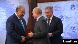 Владелец издательского дома «Коммерсантъ» Алишер Усманов (слева), Владимир Путин и глава Минобороны Сергей Шойгу (на заднем плане) на встрече в апреле