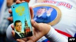 Дмитрий Медведевті жақтайтын бойжеткендер тобының бір мүшесі iPhone 4 смартфонының сыртына сол адамның суретін жапсырып алған. Мәскеу, 14 қыркүйек 2011 жыл. (Көрнекі сурет)