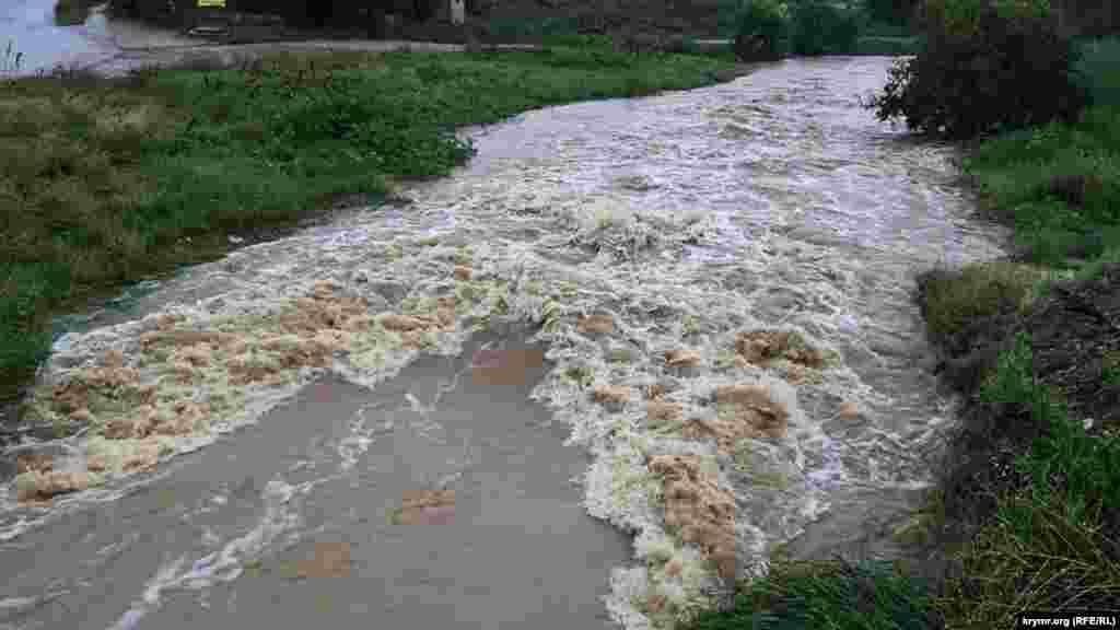 У Ленінському районі Криму в результаті зливи річка Катерлез, яка впадає в річку Мелек-Чесмі в Керчі, сильно наповнилася водою. Як повідомляє кореспондент Крим.Реалії, бурхливий потік води з річки Катерлез рухається в напрямку Керчі