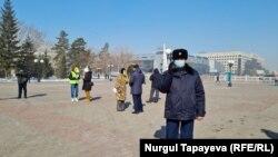Бейбіт митингіге шыққандарды камераға түсіріп тұрған полиция қызметкері. Нұр-Сұлтан, наурыз айы 2021 жыл.