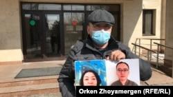 Женис Заркан, житель Алматы, с фото своих жены и сына у приемной партии «Нур Отан». Нур-Султан, 6 апреля 2021 года.