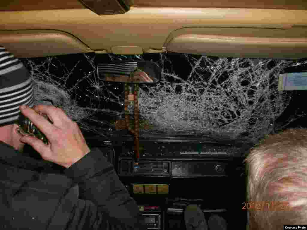 A car caught in the melee outside the prison has a shattered window reportedly broken by a police baton.