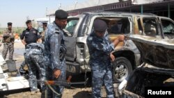 أفراد من الشرطة العراقية يتفحصون آثار إنفجار قنبلة في الحمزة