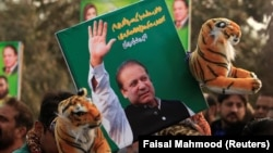 A supporter of the ruling Pakistan Muslim League (Nawaz) (PML-N) holds a picture of Nawaz Sharif outside the accountability court where he appeared on November 3.