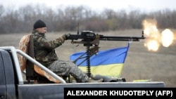 Український боєць веде вогонь в напрямку позицій російських гібридних сил біля села Бугас на Донеччині, 24 жовтня 2014 року