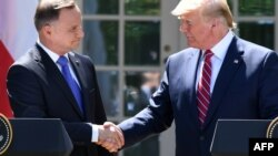 U.S. President Donald Trump (right) and Polish President Andrzej Duda shake hands after holding a joint press conference in the Rose Garden of the White House in Washington on June 12.