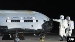 Персонал исследует военный мини-шаттл X-37B, декабрь 2010 года.